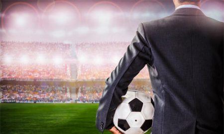 Un professionnel du sport s'est entraîné pour faire face au terrain sur un stade de Football, ballon à la main